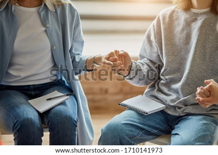 cropped photo of young unrecognizable addicts gathered together in the club of anonymous drug users, people sit holding hands, pray for speedy recovery, support Stock photo ©