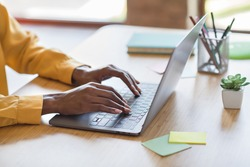 Cropped photo portrait of african american woman's hands typing on laptop in modern office indoors
