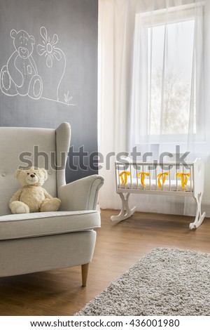 Cropped picture of an armchair and a crib in a modern nursery