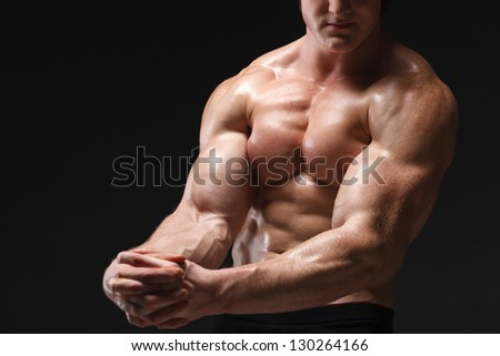 Cropped picture of muscle man posing in studio over dark background