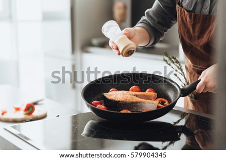 Cropped picture of young amazing woman standing in kitchen while cooking fish