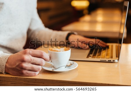 Cropped picture of young man sitting in cafe while drinking coffee and using laptop.