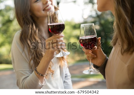 Cropped picture of young two women outdoors in park drinking wine.