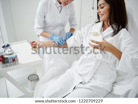 Cropped portrait of beautiful woman in white bathrobe sitting in armchair and receiving IV infusion. She is holding glass of beverage with lemon and smiling ストックフォト ©