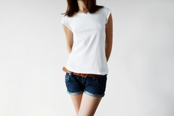 Cropped portrait of fashionable young female in denim shorts and white blank copy space T-shirt for your text or advertising content standing against white studio wall background. Lifestyle concept
