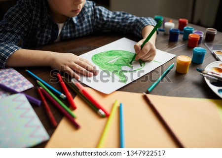 Cropped portrait of little boy drawing picture of green monster in art class, copy space