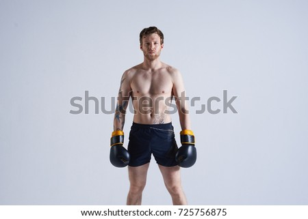 Cropped portrait of self-determined young kickboxer standing shirtless in gym, having serious confident look, ready for workout. People, determination, fitness, sports and martial arts concept. #725756875
