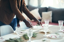 Cropped portrait of young African-American man preparing table setting while decorating dining room for Christmas party at home, copy space