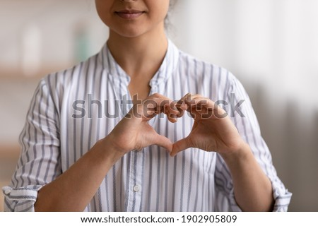 Cropped portrait of young female cardio patient expressing sincere gratitude appreciation to cardiologists volunteers charity givers. Close up of millennial woman posing to camera showing finger heart Stock photo ©