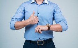 cropped punctual man in shirt check time on hand watch and show thumb up, punctuality