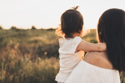 Cropped rear view of Caucasian brunette mother and child daughter embrace each other on meadow sunset. Beautiful brunette woman hugs her toddler girl and looking on sunset background. Motherhood.