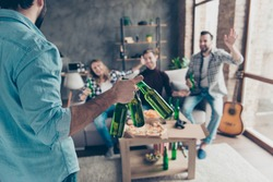 Cropped rear view of visitor bringing bottles with beer to his stylish, successful, attractive friends  who extremely happy, glad to see him with raised palm gesturing on blurred background