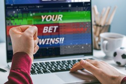 Cropped shot close up of male fist clenched with triumph in front of laptop screen. Man celebrating money win at bookmaker's website, his bet played.