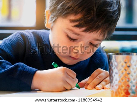 Cropped shot cute lillte boy colouring or drawning on white paper while waiting for food in restuarant, Selective focus of kid enjoy writing with green crayon on paperActivity for children with family #1180954942