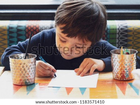 Cropped shot cute lillte boy colouring or drawning on white paper while waiting for food in restuarant, Selective focus of kid enjoy writing with green crayon on paperActivity for children with family #1183571410