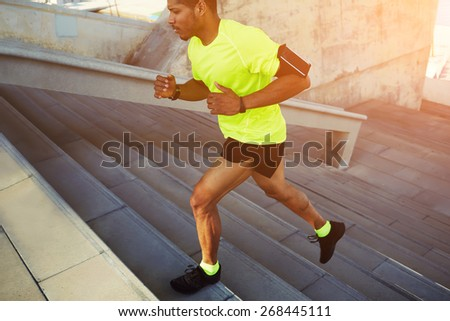 Cropped shot male dark-skinned athlete running up a flight of stairs with speed, sporty young man in fluorescent t-shirt training or working out outdoors while jogging up the steps, flare sun stock photo