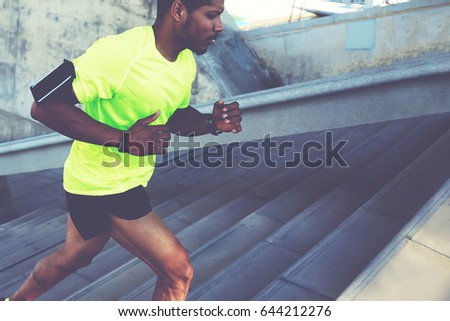 Cropped shot male dark-skinned athlete running up a flight of stairs with speed, sporty young man in fluorescent t-shirt training or working out outdoors while jogging up the steps, filtered image stock photo