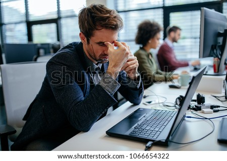 Cropped shot of a exhausted businessman sitting in front of his laptop computer in an office