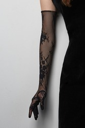 Cropped shot of a lady in a black tight dress and a black evening  glove against the gray wall. The elegant elbow glove is made of the lace fabric with floral pattern.