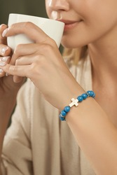 Cropped shot of a lady with turquoise beaded bracelet on her wrist. The bracelet is decorated with ivory stone cross and silver charms. The girl in beige blouse is holding white cup in her hands.