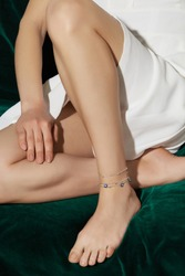 Cropped shot of a lower body part of a girl, sitting on a green velvet background. She has silver triple chain anklet, decorating with three small suspension, on her left leg.