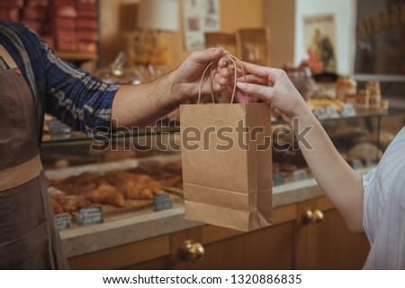 Cropped shot of a male baker wearing apron giving paper shopping bag to female customer, copy space. Woman buying food at te bakery store. Consumerism, organic food, health concept