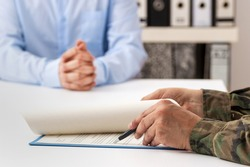 Cropped shot of a man and military man completing paperwork together at a desk