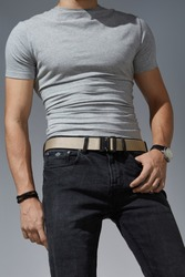 Cropped shot of a man in black jeans and a gray t-shirt on the gray background. A beige canvas belt is fitted with a black metal male buckle and a black belt loop.