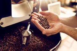 Cropped shot of a man's hands holding freshly roastd aromatic coffee beans over a modern machine used for roasting beans