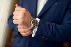Cropped shot of a man wearing elegant blue suit and a wrist watch.