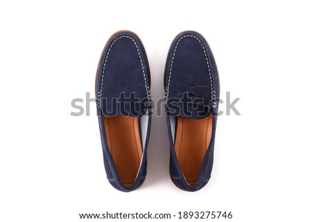 Cropped shot of a pair of dark blue penny loafers. Men's shoes isolated on white background. Suede moccasin without laces. Top view, copy space for text, flat lay. Stock fotó ©