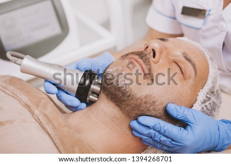 Cropped shot of a professional cosmetologist doing rf-lifting treatment for mature male client. Relaxed handsome man receiving hardware cosmetology procedure at beauty clinic #1394268701