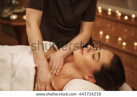 Cropped shot of a professional masseuse working. Beautiful woman lying with her eyes closed receiving full body massage at spa wellness center relaxation happiness vitality pampering skincare health #641726218
