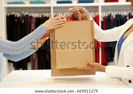 Shutterstock Cropped shot of a shop assistant handing shopping bags to a female customer copyspace buying buyer seller sale discount offer giving consumerism purchasing business lifestyle clothing boutique