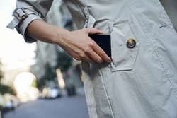 Cropped shot of a woman in grey coat putting her smartphone in pocket while standing outdoors