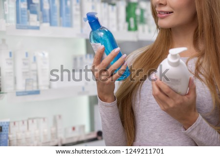 Cropped shot of a woman smiling, reading label on a bottle of medication, shopping at drugstore. Female customer examining labels on products at the pharmacy. Consumerism, buying concept
