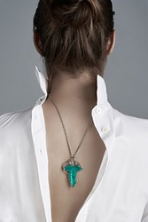 Cropped shot of a woman with elegant necklace on her back. The silver pendant on chain is made as ivy leaf with green jeweller's enamel. The lady is dressed in white unbuttoned shirt back to front.