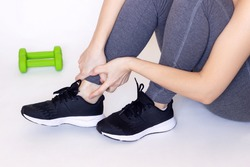 Cropped shot of a young athletic woman sitting on the floor and touching painful twisted or broken ankle with her hands. The girl twisted her leg. Sport injury, painful sprained ankle muscle