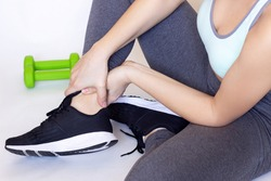 Cropped shot of a young athletic woman sitting on the floor and touching painful twisted or broken ankle with her hands. The girl twisted her leg. Sport injury, sore sprained ankle muscle
