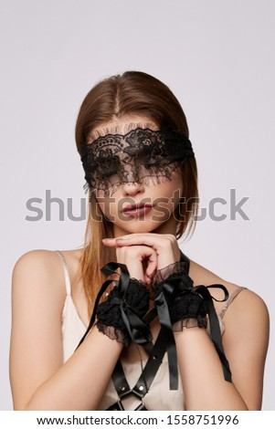 Cropped shot of a young girl, wearing beige tank top and black leather portupee. There's a lace blindfold on her eyes, lace handcuffs with lacing on her hands. The photo was taken on grey background. #1558751996