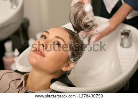Cropped shot of a young lovely woman smiling looking away, while professional hairstylist washing her long hair. Hairstylist washing hair of female client, copy space. Service, pampering concept #1278430750