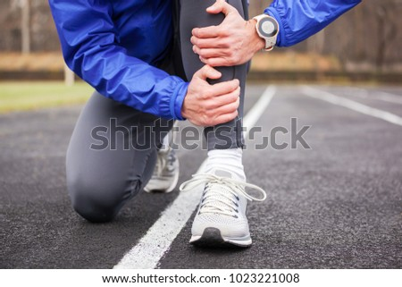 Cropped shot of a young runner holding his leg in pain. Shin splints. - Shutterstock ID 1023221008