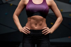 Cropped shot of active young woman in sportswear showing her sportive body abs, standing against artificial training climbing wall. Concept of sport life and rock climbing. Selective focus. Front view