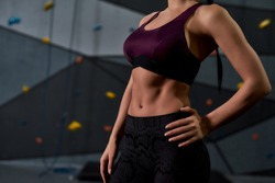 Cropped shot of active young woman in sportswear showing her sportive body, abs, standing against artificial training climbing wall. Concept of sport life and rock climbing. Selective focus