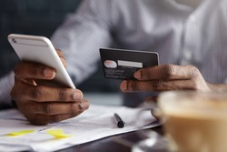 Cropped shot of African-American businessman paying with credit card online making orders via Internet. Successful black male holding plastic card making transaction using mobile banking application