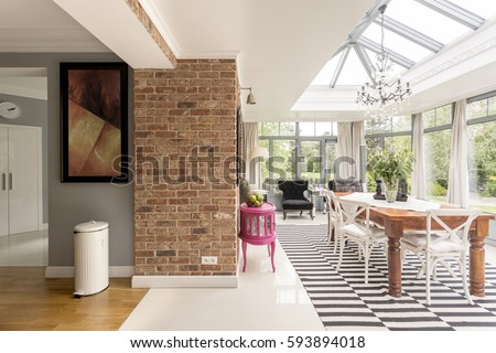Cropped shot of an open dining area with a long wooden table and glass roof and walls #593894018