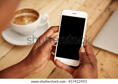Cropped shot of black female\'s hands holding mobile phone with blank copy space screen for your text message or promotional content. Young woman watching videos using cell phone sitting at cafeteria