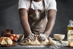 Cropped shot of black male wears apron, kneads dough as prepares delicious rolls, going to make surprise for family and treat with tasty pastry, isolated over black background. Baking concept