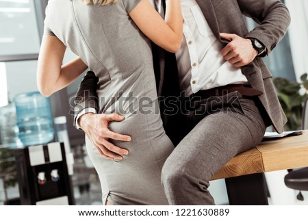 cropped shot of business colleagues hugging and flirting at workplace, office romance concept #1221630889