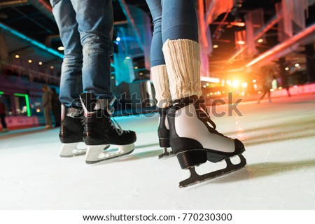 cropped shot of couple in skates ice skating on rink
